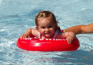 Девочка купается с красным кругом swimtrainer