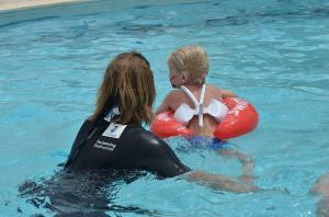 Девочка с тренером учится купается с красным кругом