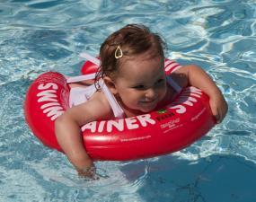 Девочка учится купается с красным кругом