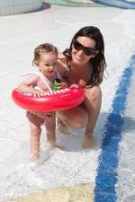 Малыш стоит с красным кругом swimtrainer