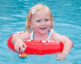 Ребёнок с красным кругом swimtrainer в воде
