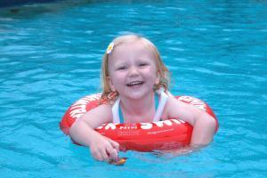 Весёлая девочка купается с красным кругом