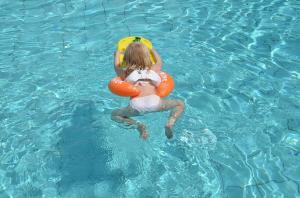Девочка купается на оранжевом круге