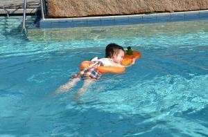 Мальчик плавает на оранжевом круге