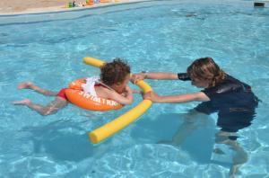 Малыш учится плавать на оранжевом круге