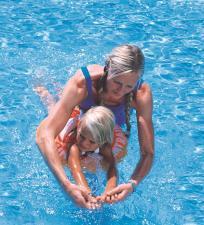 Тренер учит девочку плавать на оранжевом круге