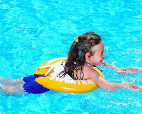 Девочка купается с желтым кругом swimtrainer