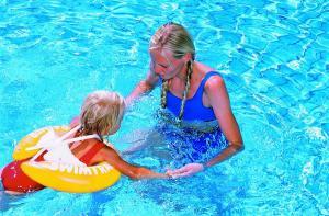 Девочка учится купается с желтым кругом