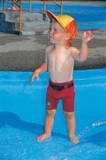 Мальчик у бассейна в шортах
