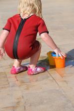 Девочка одетая в малый комбинезон играет в формочки