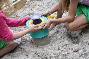 Дети на песке строят башенку формочкой quut alto