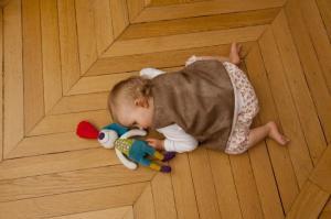 Малыш играет с игрушкой кролик джеф с погремушкой