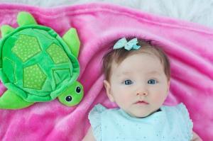Девочка лежит на одеяле с игрушкой