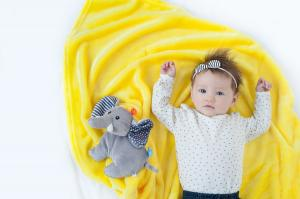 Ребёнок лежит на одеяле с игрушкой слон
