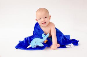 Малыш сидит в одеяле с игрушкой кит