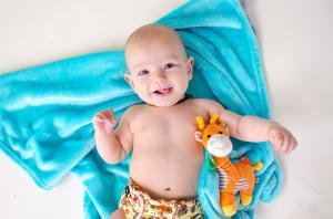 Ребёнок лежит на одеяле с игрушкой жираф