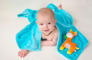 Ребёнок укрыт одеялом с игрушкой жираф