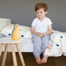 Мальчик сидит на кровати рядом с ночником пэм синий