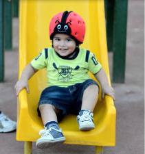 Ребёнок на горке в шлеме safeheadbaby красный