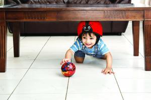 Ребёнок под столом в шлеме safeheadbaby красный