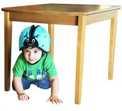 Ребёнок под столом в шлеме safeheadbaby синий