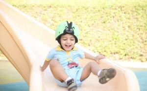 Ребёнок на горке в шлеме safeheadbaby зелёный