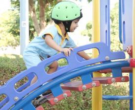 Ребёнок на лестнице в шлеме safeheadbaby зелёный