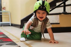 Ребёнок в шапке-шлем safeheadbaby зелёный