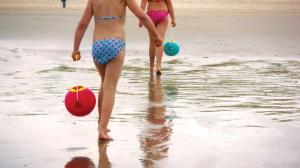 Дети на пляже с круглыми ведёрками