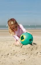 Девочка играет с круглым ведёрком