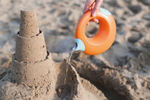 На пляже поливают из лейки песок
