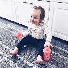 Девочка сиди на полу с бутылочкой twistshake