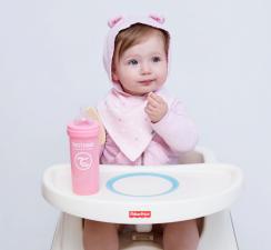Девочка за столом с розовой бутылочкой