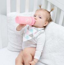 Малыш кушает из нежно-розовой бутылочки
