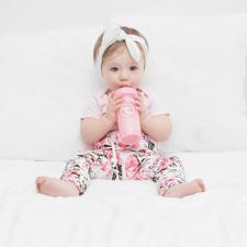 Малыш пьет из розовой бутылочки twistshake
