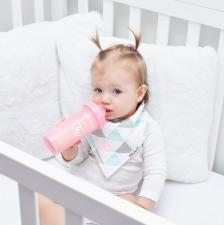 Ребенок в кроватке с розовой бутылочкой